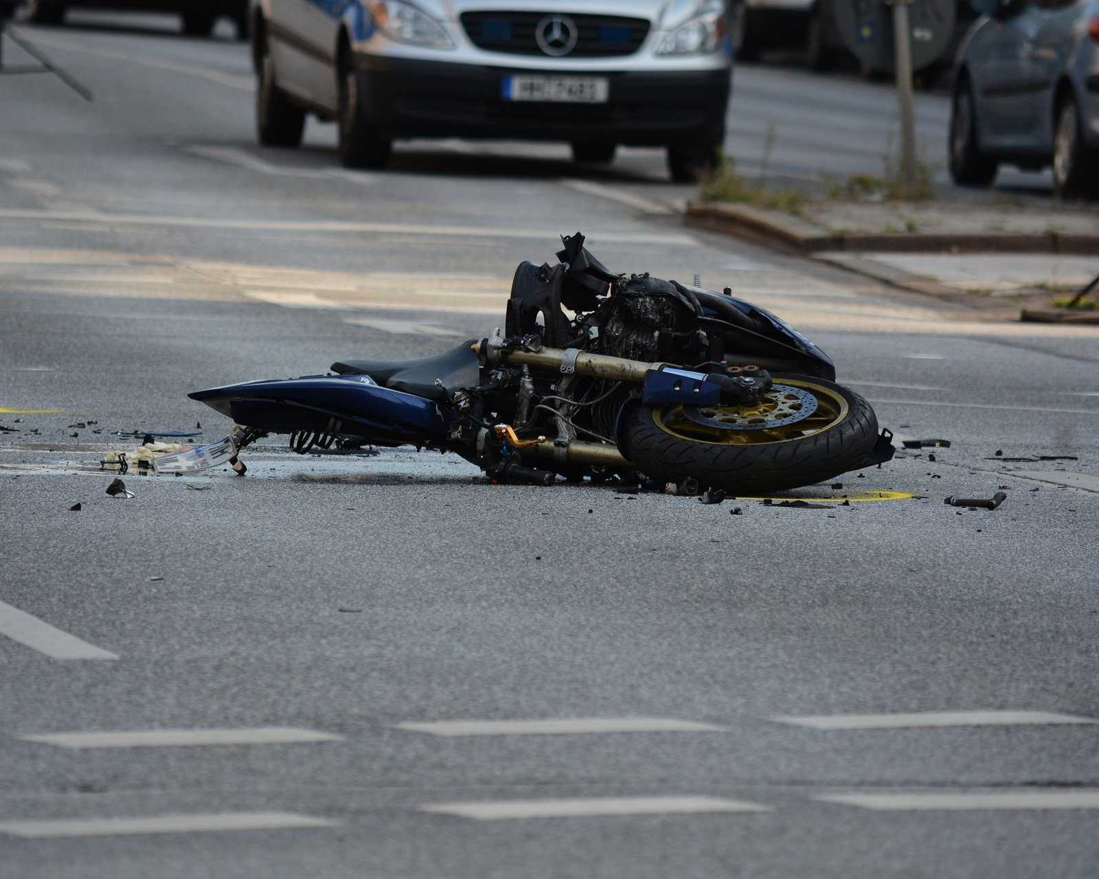 Crashed motocycle laying on the ground in the middle of the road - Spitzer Legal Motorcycle Accident Practice Area