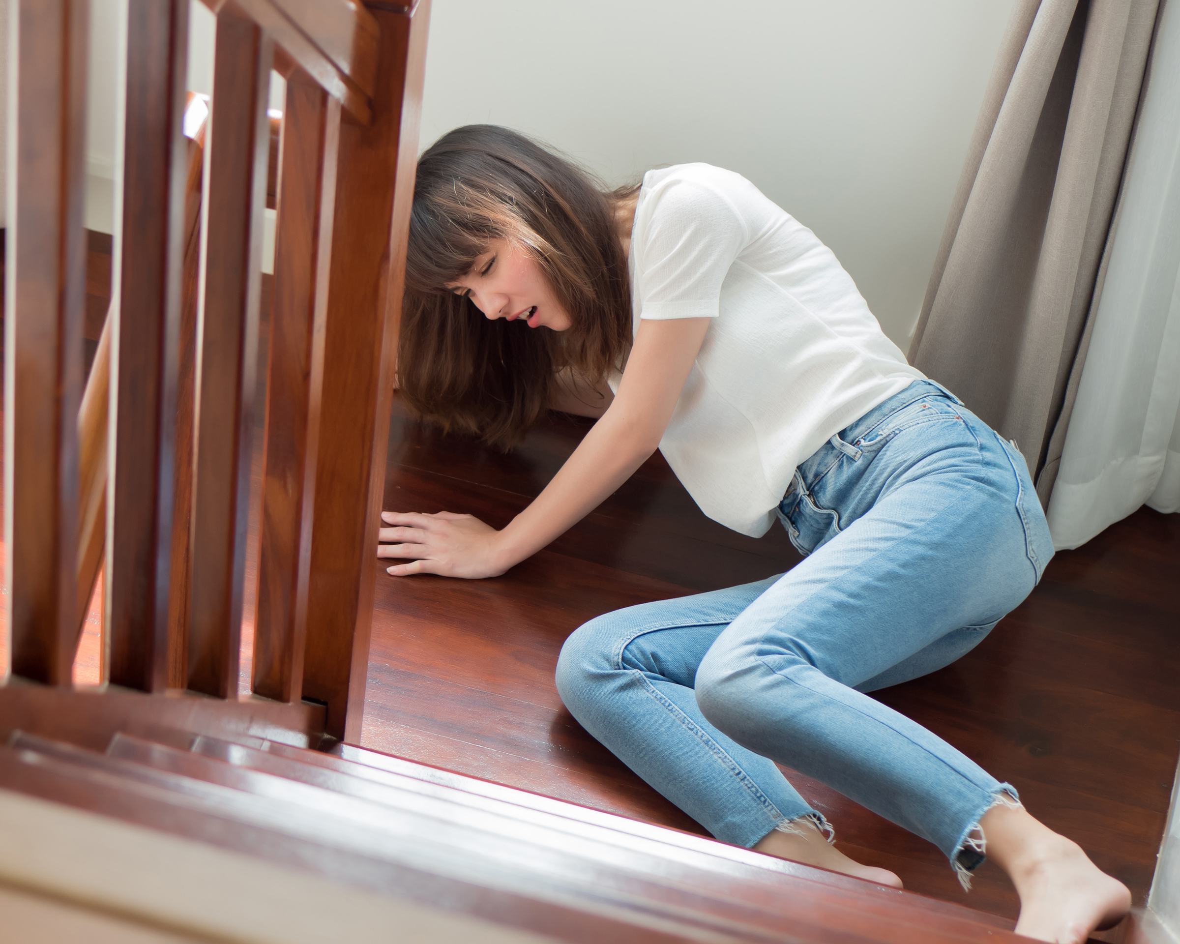 Woman in blue jeans and a white top laying on ground after falling down stairs - Spitzer Legal Slip & Fall Injury Practice Area